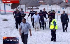 Полиция уносит тело смертника с пляжа. Кадр телеканала ТВЦ