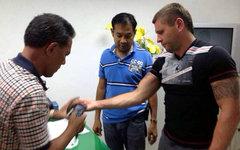 У Олега Фоменко (справа) снимают опечатки пальцев. Фото с сайта phuketwan.com