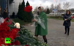 Соболезнующие несут цветы на место трагедии. Кадр телеканала Russia Today