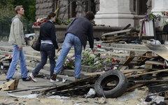 Молодые люди возлагают цветы в память о погибших в результате пожара в Доме проф