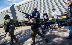 Сотрудники миссии ОБСЕ у поезда с телами погибшим. © РИА Новости, Андрей Стенин